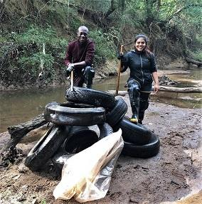 Volunteers in front of river with tires